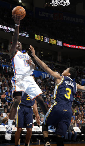 Photo - Oklahoma City's Reggie Jackson (15) shoots a lay up over Utah's Trey Burke (3) during the NBA game between the Oklahoma City Thunder and the Utah Jazz at the Chesapeake Energy Arena, Sunday, Nov. 24, 2013. Photo by Sarah Phipps, The Oklahoman