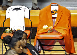 Photo - Coach Kurt Budkey's orange blazer hangs from a seat on the sideline during the memorial service for Oklahoma State head basketball coach Kurt Budke and assistant coach Miranda Serna at Gallagher-Iba Arena on Monday, Nov. 21, 2011 in Stillwater, Okla. Photo by Chris Landsberger