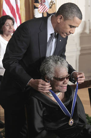 """Photo - FILE - This Feb. 15, 2011 file photo shows President Barack Obama kissing author and poet Maya Angelou after awarding her the 2010 Medal of Freedom during a ceremony in the East Room of the White House in Washington. President Barack Obama said Wednesday's passing of poet and author Maya Angelou has dimmed """"one of the brightest lights of our time."""" Obama said in a statement that he and first lady Michelle Obama will always cherish the time they were privileged to spend with Angelou. He says Angelou had the ability to remind us that we are all God's children and that we all have something to offer. (AP Photo/Pablo Martinez Monsivais, File)"""