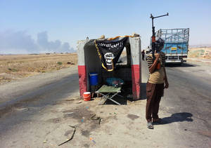Photo - FILE - In this file photo taken Thursday, June 19, 2014, an al-Qaida-inspired militant stands guard at a checkpoint captured from the Iraqi Army outside Beiji refinery, some 250 kilometers (155 miles) north of Baghdad, Iraq. The al-Qaida breakaway group that has seized much of northern Syria and huge tracks of neighboring Iraq formally declared the creation of an Islamic state on Sunday, June 29, in the territory under its control. (AP Photo, File)