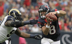 Photo - Houston Texans quarterback Matt Schaub (8) tries to avoid a tackle by St. Louis Rams defensive tackle Michael Brockers during an NFL football game   Sunday, Oct. 13, 2013, in Houston. St. Louis defeated Houston 38-13. (AP Photo/ The Courier, Jason Fochtman)