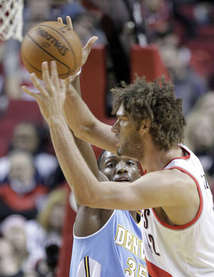 Photo - Denver Nuggets forward Kenneth Faried, left, defends against Portland Trail Blazers center Robin Lopez during the first half of an NBA basketball game in Portland, Ore., Saturday, March 1, 2014. (AP Photo/Don Ryan)