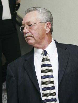 Photo - Former Custer County Sheriff Mike Burgess, leaves the courthouse during a break for lunch in his trial in Arapaho, Okla., Tuesday, Aug. 12, 2008. (AP Photo)