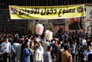 "photo -   Egyptian protesters gather in Tahrir Square in Cairo, Egypt, Sunday, Nov. 25, 2012. President Mohammed Morsi edicts, which were announced on Thursday, place him above oversight of any kind, including that of the courts. The move has thrown Egypt's already troubled transition to democracy into further turmoil, sparking angry protests across the country to demand the decrees be immediately rescinded. The banner in Arabic, top center, reads, ""members of the Muslim Brotherhood are not allowed."" (AP Photo/Ahmed Gomaa)"