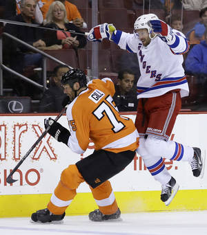 Photo - New York Rangers' Dominic Moore, right, collides with Philadelphia Flyers' Hal Gill during the first period of a preseason NHL hockey game, Tuesday, Sept. 17, 2013, in Philadelphia. (AP Photo/Matt Slocum)
