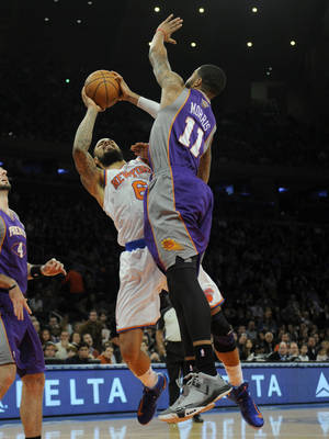 photo - New York Knicks' Tyson Chandler, left, is fouled by Phoenix Suns' Markieff Morris in the first quarter of an NBA basketball game at Madison Square Garden in New York, Sunday, Dec. 2, 2012. (AP Photo/Henny Ray Abrams)
