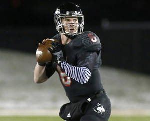 Photo - FILE - This Nov. 26, 2013 file photo shows Northern Illinois quarterback Jordan Lynch looking to pass during the first half of an NCAA football game against Western Michigan in DeKalb, Ill.  Lynch and Ball State quarterback Keith Wenning have already forgotten about their college rivalry. On Wednesday, Feb. 19, 2014, the two quarterbacks find themselves working toward the same goal and pushing one another as training partners and friends. (AP Photo/Charles Rex Arbogast, file)
