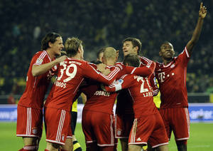 Photo - Bayern's Thomas Mueller, second right, celebrates with teammates after scoring the third goal during the German Bundesliga soccer match between Borussia Dortmund and Bayern Munich in Dortmund, Germany, Saturday, Nov. 23, 2013. Dortmund was defeated by Bayern 0-3. (AP Photo/Martin Meissner)