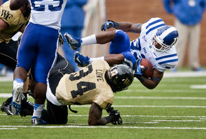 Photo -   Duke's Desmond Scott is tripped up by Wake Forest's Duran Lowe (34) during the first half of an NCAA college football game in Winston-Salem, N.C., Saturday, Sept. 29, 2012. (AP Photo/Winston-Salem Journal, Lauren Carroll)
