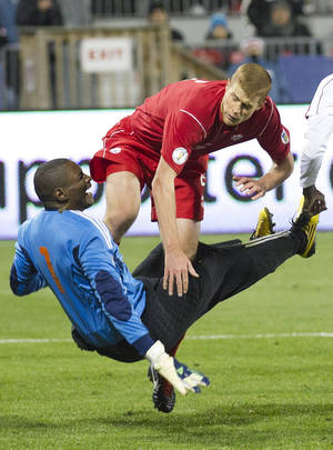 Photo -   Canada's Andre Hainault and Cuba goalkeeper OdelAn Molina collide during the second half of a World Cup qualifying soccer match in Toronto on Friday, Oct. 12, 2012. (AP Photo/The Canadian Press, Nathan Denette)