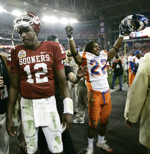 Photo - Paul Thompson walks off the field as Kyle Wilson of Boise State celebrates during the University of Oklahoma Sooners (OU) college football game against Boise State University Broncos (BSU) in the Fiesta Bowl at the University of Phoenix Stadium, on Monday, Jan. 1, 2007, in Glendale, Ariz.  By Bryan Terry, The Oklahoman