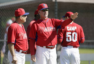 Photo - Philadelphia Phillies manager Ryne Sandberg talks with bench coach Larry Bowa, left, during spring training baseball practice Wednesday, Feb. 19, 2014, in Clearwater, Fla. (AP Photo/Charlie Neibergall)