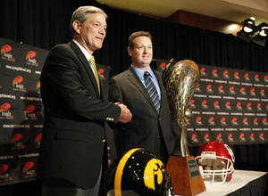 Photo - Iowa head coach Kirk Ferentz and Oklahoma head coach Bob Stoops pose in front of the Insight Bowl trophy during a press conference for the Insight Bowl at the Camelback Inn in Paradise Valley, Ariz.,  Thursday, Dec. 29, 2011. Photo by Sarah Phipps, The Oklahoman