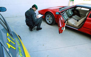 Photo -   This undated handout photo provided on Oct. 24, 2012 by the the Guardia di Finanza, Italy's financial police corps, shows a tax police officer next to a confiscated Ferrari, at the Guardia di Finanza quarters, in Pescara, Italy. Good plumbers might be worth their weight in gold, but when one was spotted zipping around near the town of Pescara in a bright red Ferrari, Italian tax police were fast on his trail. Eradicating entrenched, endemic tax evasion is crucial to Premier Mario Monti's quest to keep Italy from succumbing to the European debt crisis, and it is critical to fellow euro-zone members in more dire straits, such as Greece and Spain. (AP Photo/Courtesy of the Guardia di Finanza, ho)