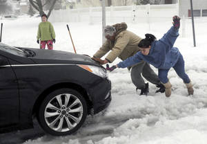 Photo - Candice Genega, right, loses her footing while helping Charlie McKenna push a stranded motorist out of heavy snow along an unplowed street in Centereach, N.Y. on Monday, Feb. 11,  2013. (AP Photo/Newsday, Thomas A. Ferrara) NYC OUT
