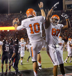 Photo - Oklahoma State 's Clint Chelf (10) and Tracy Moore (87) celebrate Chelf's touchdown during the college football game between the Oklahoma State University Cowboys (OSU) and the Texas Tech University Red Raiders (TTU) at Jones AT&T Stadium in Lubbock, Tex. on Saturday, Nov. 2, 2013.  Photo by Chris Landsberger, The Oklahoman