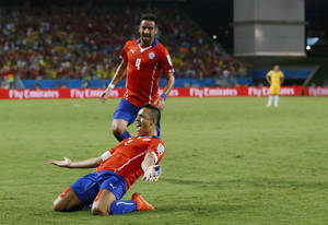 Photo - Chile's Mauricio Isla (4) watches as Alexis Sanchez celebrates after scoring his side's first goal during the first half of the group B World Cup soccer match between Chile and Australia in the Arena Pantanal in Cuiaba, Brazil, Friday, June 13, 2014.  (AP Photo/Kirsty Wigglesworth)