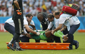 Photo - Nigeria's Michael Babatunde is lifted from the pitch before being taken off the field during the group F World Cup soccer match against Argentina at the Estadio Beira-Rio in Porto Alegre, Brazil, Wednesday, June 25, 2014. (AP Photo/Jon Super)