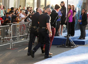 "Photo - A fan is walked off carpet in handcuffs after allegedly attacking Brad Pitt at the world premiere of ""Maleficent"" at the El Capitan Theatre on Wednesday, May 28, 2014, in Los Angeles.  (Photo by Matt Sayles/Invision/AP)"