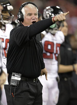 Photo - Atlanta Falcons coach Mike Smith points toward the field during the second half of the Falcons' NFL football game against the San Francisco 49ers in San Francisco, Monday, Dec. 23, 2013. (AP Photo/Tony Avelar)