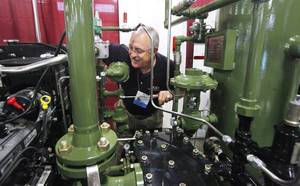photo - Bob Steed, Yukon, looking at a natural gas compressor in the Sertco Industries booth at the Oklahoma Oil & Gas Expo being held at State Fair Park in Oklahoma City Thursday, Oct. 4, 2012.  Sertco Industries is located in Okemah, Oklahoma. Photo by Paul B. Southerland, The Oklahoman