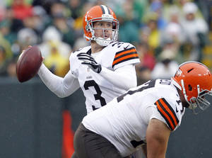 Photo - FILE - In this Oct. 20, 2013, file photo, Cleveland Browns' Brandon Weeden drops back during the first half of an NFL football game against the Green Bay Packers in Green Bay, Wis. The Dallas Cowboys added free agent Weeden on a two-year contract Monday, March 17, 2014. (AP Photo/Mike Roemer, File)