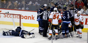 Photo - Winnipeg Jets' goaltender Al Montoya (35) lays on the ice after being crushed by Calgary Flames' Lee Stempniak (22) during third period NHL hockey action in Winnipeg Monday, Nov. 18, 2013. (AP Photo/The Canadian Press, Trevor Hagan)