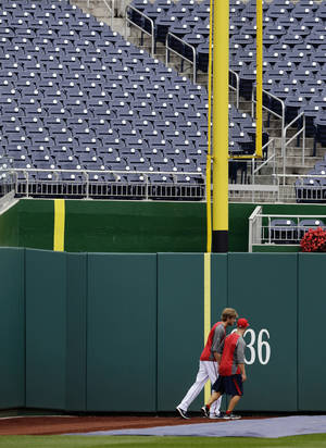 Photo -   Washington Nationals starting pitcher Ross Detwiler, left, starts to run with assistant strength and conditioning coach Matt Eiden under the left-field foul pole during a baseball workd for the National League division series at Nationals Park, Tuesday, Oct. 9, 2012, in Washington. Left field at the ballpark has an odd ground rule: If a ball lands in fair territory and bounces between the two lines, it results in a ground-rule double. But if a ball lands in fair territory and bounces on or to the left of the extra line that sits in foul territory, that ball is in play. (AP Photo/Alex Brandon)