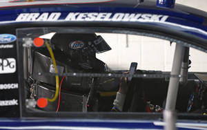 Photo - Brad Keselowski checks his phone as he sits in his car as the crew works on it during testing for the NASCAR Sprint Cup auto racing series at Charlotte Motor Speedway in Concord, N.C., Tuesday, Dec. 11, 2012. (AP Photo/Chuck Burton)
