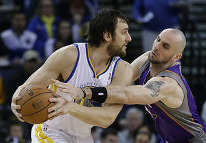 Photo - Golden State Warriors' Andrew Bogut, left, keeps the ball from Phoenix Suns' Marcin Gortat in the first half of an NBA basketball game Saturday, Feb. 2, 2013, in Oakland, Calif. (AP Photo/Ben Margot)