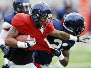 Photo -   Mississippi's Randall Mackey (1) is tackled by Anthony Sandifer (23) during a scrimmage at NCAA college football practice at Vaught-Hemingway Stadium in Oxford, Miss. on Saturday, Aug. 18, 2012. (AP Photo/Oxford Eagle, Bruce Newman) MANDATORY CREDIT, MAGS OUT, NO SALES