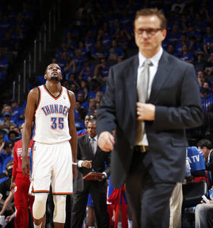 Photo - Oklahoma City's Kevin Durant (35) walks to the bench as coach Scott Brooks walks on the court for a timeout during Game 1 of the Western Conference semifinals in the NBA playoffs between the Oklahoma City Thunder and the Los Angeles Clippers at Chesapeake Energy Arena in Oklahoma City, Monday, May 5, 2014. Photo by Sarah Phipps, The Oklahoman