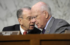 photo - FILE - In this Feb. 13, 2013 file photo, Senate Judiciary Committee Chairman Sen. Patrick Leahy, D-Vt., right, talks with the committee's ranking Republican Sen. Charles Grassley, R-Iowa, on Capitol Hill in Washington. Tuesday March 12, 2013 meeting comes five days after the panel approved Congress' first gun control measure since December's carnage at a Newtown, Conn., elementary school that left 26 students and educators dead. That bill, by the Judiciary Committee's chairman, Sen. Patrick Leahy, D-Vt., and others, establishes long prison terms for illegal gun traffickers and straw purchasers, people who buy a firearm for criminals or others forbidden to buy one. (AP Photo/Susan Walsh, File)