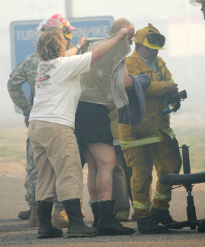 Photo - David Milby, center, was injured fighting grassfires near Wellston Thursday. Photo by Steve Gooch
