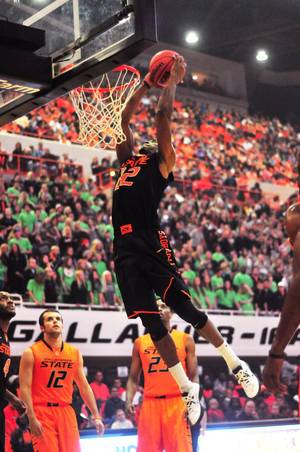 Photo - Oklahoma State guard Markel Brown dunks during Oklahoma State's Homecoming and Hoops event at Gallagher Iba Arena in Stillwater on October 18, 2013. Photo by KT King/For the Oklahoman