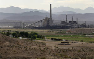 Photo -   FILE - In this Monday, May 14, 2012, file photo, the Reid-Gardner power station is seen near a farm on the Moapa Indian Reservation, in Moapa, Nev. Tribal neighbors of a coal-fired power plant outside Las Vegas are taking complaints about air quality to a federal appeals court in San Francisco. Moapa Band of Paiute Indians leader William Anderson said Monday the tribe hopes the 9th U.S. Circuit Court of Appeals will order the federal Environmental Protection Agency to adopt a more stringent air standard than the one the agency approved in August for the Reid Gardner Generating Station. (AP Photo/Julie Jacobson,file)