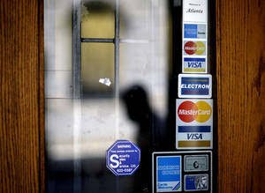 photo -   FILE-In this July 18, 2012 file photo, credit card logos are seen on a downtown storefront as a pedestrian passes in Atlanta. Egan-Jones announced Friday, Sept. 14, 2012, that it is downgrading its rating on U.S. debt to AA- from AA, citing Federal Reserve plans to try to stimulate the economy. The credit rating agency says the Fed's plans to buy mortgage bonds will likely hurt the economy more than help it. Egan-Jones says the plan will reduce the value of the dollar and raise the price of oil and other commodities, hurting businesses and consumers. (AP Photo/David Goldman, File)
