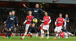 Photo - Manchester United's Chris Smalling, centre, watches as the ball goes past and he misses an chance on goal during their English Premier League soccer match between Arsenal and Manchester United at the Emirates stadium in London, Wednesday, Feb. 12, 2014. (AP Photo/Alastair Grant)
