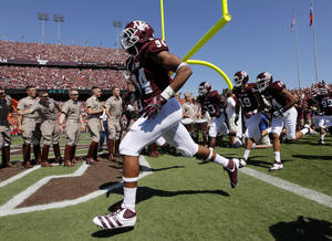Photo - Damontre Moore (94) and the Texas A&M Aggies take the field before a college football game between the Oklahoma State Cowboys (OSU) and the Texas A&M Aggies at Kyle Field in College Station, Texas, Saturday, Sept. 24, 2011. Photo by Nate Billings, The Oklahoman  ORG XMIT: KOD