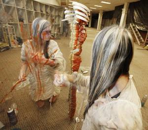Photo - Katelyn Hooper sprays color in her hair as she prepares to work in a haunted house in Crossroads mall in Oklahoma City Friday. <strong>Steve Gooch</strong>