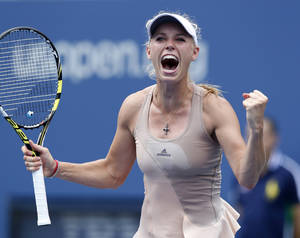 Photo - Caroline Wozniacki, of Denmark, reacts after defeating Maria Sharapova, of Russia, during the fourth round of the 2014 U.S. Open tennis tournament, Sunday, Aug. 31, 2014, in New York. (AP Photo/Kathy Willens)