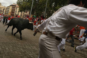 "Photo - Revelers run in front of a Victoriano del Rio ranch fighting bull during the running of the bulls of the San Fermin festival, in Pamplona, Spain, Wednesday, July 9, 2014. Revelers from around the world arrive in Pamplona every year to take part on some of the eight days of the running of the bulls glorified by Ernest Hemingway's 1926 novel ""The Sun Also Rises."" (AP Photo/Daniel Ochoa de Olza)"