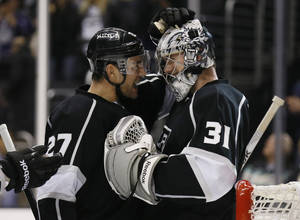 Photo - Los Angeles Kings' goaltender Martin Jones (31) celebrates a shutout with teammate Alec Martinez, left, after an NHL hockey game against the Edmonton Oilers in Los Angeles, Tuesday, Dec. 17, 2013. The Kings won 3-0. (AP Photo/Danny Moloshok)