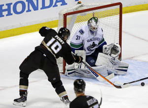 Photo - Vancouver Canucks goalie Eddie Lack (31) defends as Anaheim Ducks right winger Corey Perry (10) attacks in the second period of an NHL hockey game in Anaheim, Calif., Sunday, Jan. 5, 2014. (AP Photo/Reed Saxon)