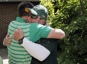 photo - Retiring teacher Dan O'Halloran, right, hugs nephew Sean O'Halloran during a recent retirement ceremony honoring the teacher in the outdoor classroom at Central Junior High School in Moore. The school has renamed the outdoor classroom the O'Halloran Classroom in honor of the seventh-grade science teacher. Photo by Nate Billings, The Oklahoman <strong>NATE BILLINGS - NATE BILLINGS</strong>