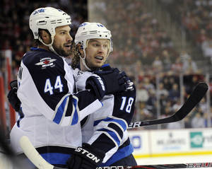 Photo - Winnipeg Jets' Zach Bogosian (44) celebrates his goal with Bryan Little during the first period of an NHL hockey gameNew Jersey Devils Sunday, Feb. 24, 2013, in Newark, N.J. (AP Photo/Bill Kostroun)