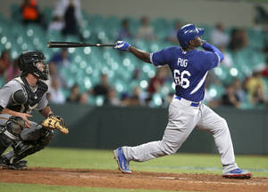 Photo - Los Angeles Dodgers' Yasiel Puig hits a two-run home run during their exhibition baseball game against Team Australia at the Sydney Cricket Gground in Sydney, Thursday, March 20, 2014. The Arizona Diamondbacks and the Dodgers open the Major League Baseball regular season with games on Saturday and Sunday. (AP Photo/Rick Rycroft)