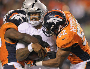 Photo - Oakland Raiders quarterback Terrelle Pryor (2) is sacked by the Denver Broncos in the fourth quarter of an NFL football game, Monday, Sept. 23, 2013, in Denver. (AP Photo/Jack Dempsey)