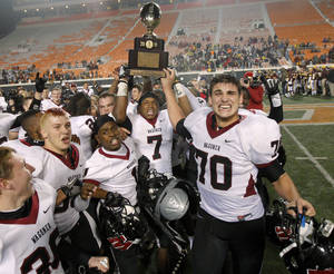 Photo - Wagoner's Kevin Peterson holds up the state championship trophy beside Heath Wilson, right, and Lawrence Evitt after beating Clinton 23-0 in the class 4A state championship high school football game at Boone Pickens Stadium  in Stillwater, Okla., Friday, Dec. 2, 2011. Photo by Bryan Terry, The Oklahoman