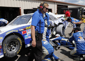 Photo -   Crew members look at Mark Martin's car in the garage area during the NASCAR Sprint Cup Pure Michigan 400 auto race at Michigan International Speedway, Sunday, Aug. 19, 2012, in Brooklyn, Mich. (AP Photo/Bob Brodbeck)